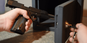 a hand with a gun putting on the gun safe